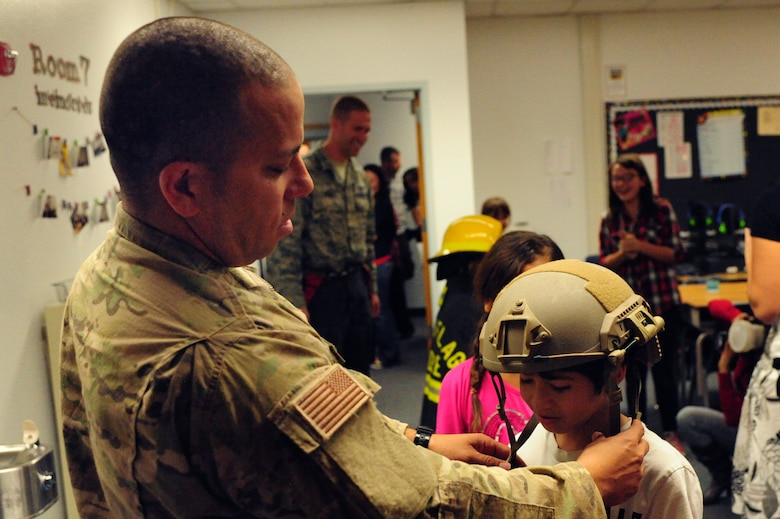 Tech. Sgt. Lawrence Dizon, 66th Weapons Squadron communications equipment technician, assists 5th grade students in trying on some equipment during a Veteran's Day celebration Nov. 8, 2013 at Doris French Elementary School in Las Vegas. Airmen from a variety of career fields volunteered their time to celebrate Veteran's Day with the students and share some of their military experiences. (U.S. Air Force photo by Airman 1st Class Joshua Kleinholz)