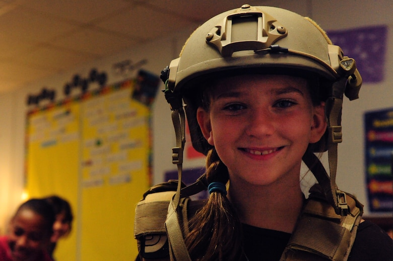 Fifth grade student Rachael Rodriguez tries on a combat helmet and vest during a demonstration given by Airmen Nov. 8, 2013 at Doris French Elementary in Las Vegas.  Throughout the day, 16 Airmen rotated through classrooms giving presentations about their career fields and answering questions about life in the military. (U.S. Air Force photo by Airman 1st Class Joshua Kleinholz)