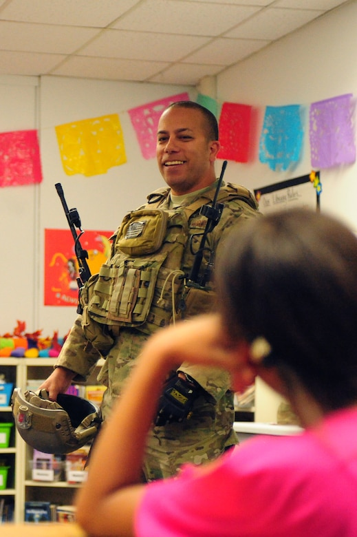Tech. Sgt. Lawrence Dizon, 66th Weapons Squadron communications equipment technician, gives a presentation to fight grade students about his Air Force experiences during a Veteran's Day celebration Nov. 8, 2013 at Doris French Elementary School in Las Vegas. Throughout the day, 16 Airmen rotated through classrooms giving presentations about their career fields and answering questions about life in the military. (U.S. Air Force photo by Airman 1st Class Joshua Kleinholz)