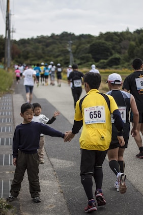A Hagi Iwami Airport Half Marathon participant gives a high-five to a Japanese child during the race Oct. 20, 2013. Staff members could be seen around every turn of the race, providing medical assistance or food to those who needed it.