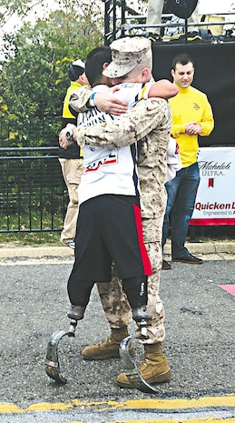Former Cpl. Carlos Torres embraces 2nd Lt. Brian Parker, his onetime platoon sergeant, at the Marine Corps Marathon 10K finish line. It was Quantico's most popular picture from the event.