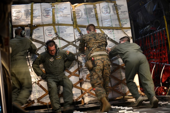 Airmen and Marines load humanitarian aid onto a C-130 Hercules aircraft during Operation Damayan Nov. 18, 2013, at Clark Air Base, Republic of the Philippines. Five C-130 crews from Yokota Air Base, Japan, are conducting multiple nighttime sorties that each carry up to 42,000 pounds of rolling cargo in the form of humanitarian aid and relief supplies from Manila to Tacloban, Philippines.