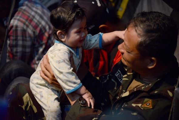 A Philippine army soldier comforts a baby on an Air Force C-130 Hercules aircraft Nov. 19, 2013, during an evacuation mission in support of Operation Damayan at Villamor Air Base, Republic of the Philippines. Operation Damayan is a humanitarian aid and disaster relief operation led by the Philippine government and supported by a multinational response force.