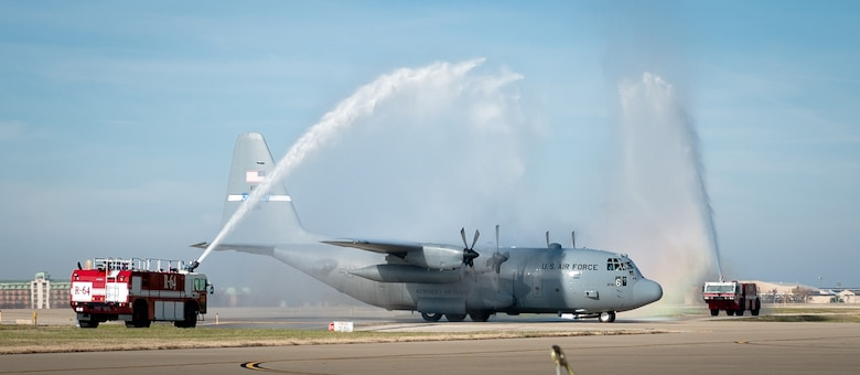 """Fire trucks spray a symbolic salute at the Kentucky Air National Guard Base in Louisville, Ky., as a C-130 Hercules aircraft piloted by Lt. Col. Scott Wilson taxies to its parking spot Nov. 20, 2013. Wilson, who is set to retire Jan 31, 2014, was completing his final, or """"fini,"""" flight in the C-130. (U.S. Air National Guard photo by Maj. Dale Greer)"""