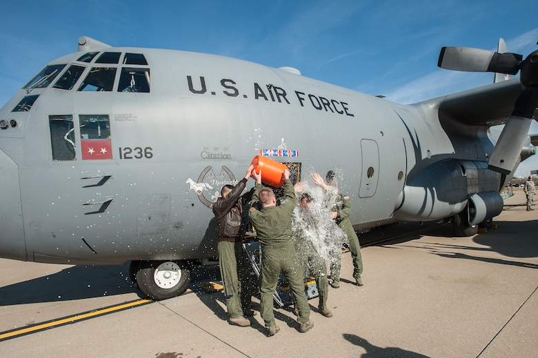 """Members of the 123rd Airlift Wing douse Lt. Col. Scott Wilson, a Kentucky Air National Guard C-130 pilot, with water as he exits the aircraft for the last time at the Kentucky Air National Guard Base in Louisville, Ky., on Nov. 20, 2013. Wilson, who is set to retire Jan. 31, 2014, was completing his final, or """"fini,"""" flight. (U.S. Air National Guard photo by Maj. Dale Greer)"""