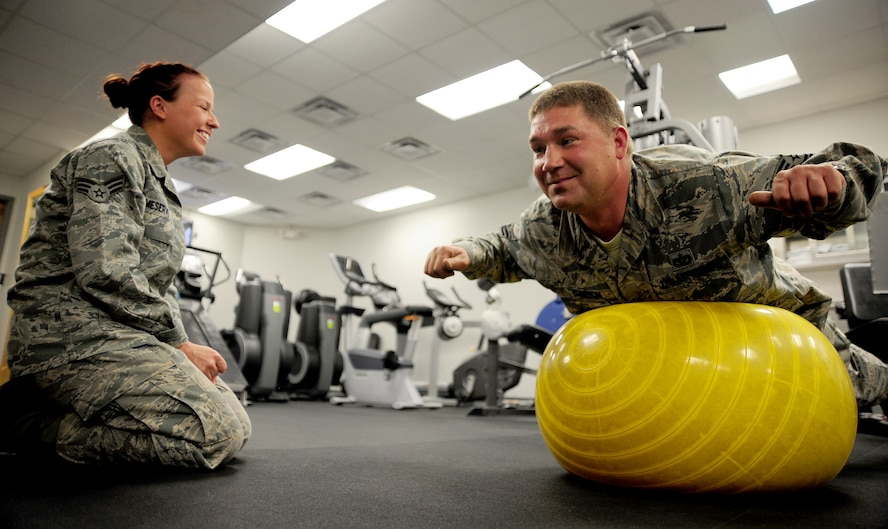 U.S. Air Force Senior Airman India Meserve, 509th Medical Operations Squadron physical therapy technician, shares a laugh with U.S. Air Force Tech. Sgt. Thomas Dawson, 509th Civil Engineer Squadron, during a physical therapy exercise session at Whiteman Air Force Base, Mo., Nov. 8, 2013. Air Force physical therapy technicians perform a variety of duties, including the evaluation and treatment of patients, therapeutic training and serving as consultants to medical staff members. (U.S. Air Force photo by Staff Sgt. Nick Wilson/Released)