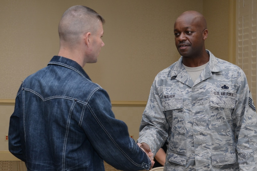 America's Got Talent contestant Jimmy Rose shakes hands with Master Sgt. Julius Walker, 437th Maintenance Squadron resource advisor,  Nov. 15, 2013, at Joint Base Charleston – Air Base, S.C. Rose, a country singer, songwriter and guitarist, finished in 3rd place on the shows eighth season. Rose is a U.S. Marine veteran originally from Pineville, Ky.(U.S. Air Force photo/ Airman 1st Class Chacarra Neal)