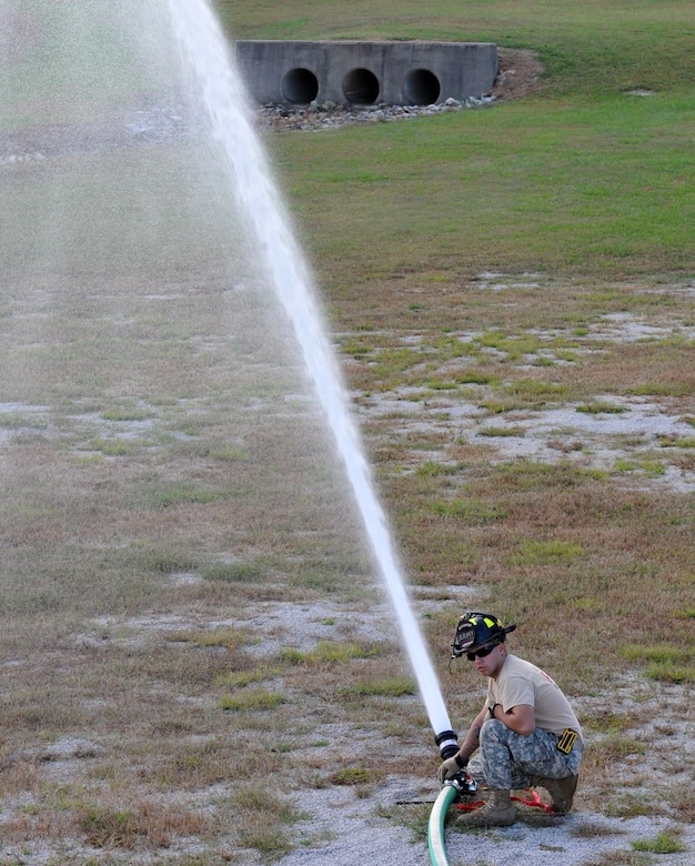 U.S. Army Specialist James Knight, a member of the North Carolina Army National Guard, 430th Engineer Fire-Fighting Team, utilizes various nozzle settings and proper water application during a training exercise held at the 145th Air National Guard Regional Training Site in New London, N.C., October 23, 2013.  In the wake of the Federal Government shutdown many North Carolina State firefighters were furloughed and Army Guard Firefighters assigned to 430th and 677th Engineer Fire Fighting Teams were mobilized to assist in support of Fire Protection at Charlotte-Douglas International Airport and Stanly County Airport. (Air National Guard photo by Master Sgt. Patricia F. Moran/Released)