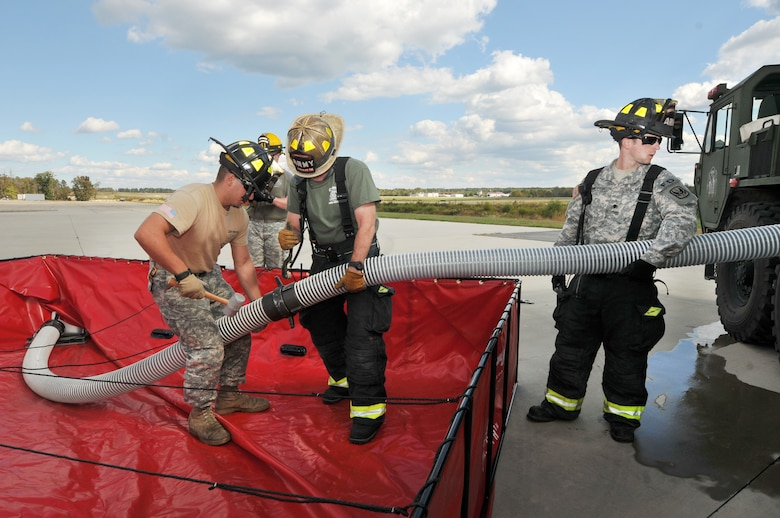 U.S. Army Specialist Gindelsperger holding the suction, Staff Sgt. Tim Layton, Non-Commissioned Officer in Charge with spanner wrench and Specialist Knight holding mallet, all from the North Carolina Army National Guard, 430th Engineer Fire-Fighting Team prepare to attach a hose to pump water into a US Army's Tactical Fire Fighting Truck during a training exercise held at the 145th Air National Guard Regional Training Site in New London, N.C., October 23, 2013.  In the wake of the Federal Government shutdown many North Carolina State firefighters were furloughed and Army Guard Firefighters assigned to 430th and 677th Engineer Fire Fighting Teams were mobilized to assist in support of Fire Protection at Charlotte-Douglas International Airport and Stanly County Airport. (Air National Guard photo by Master Sgt. Patricia F. Moran/ Released)