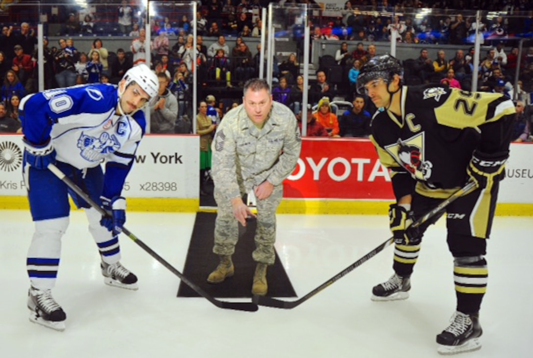 New York Air National Guard Chief Master Sgt. Chistopher Cushman (middle) of the 174th Attack Wing participates in a puck drop before the Syracuse Crunch game on 15 Nov 2013. The Syracuse Crunch hosted the Wilkes-Barre/Scranton Penguins in a American Hockey League (AHL) game at the Onondaga County War Memorial (Photo by Scott Thomas)