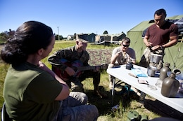 Sgt. Greg Wubben, a civil affairs non-commissioned officer with 1st Civil Affairs Group, I Marine Expeditionary Force, from Ridgefield, Wash., plays guitar and talks with members of the New Zealand Defence Force in the field during exercise Southern Katipo 2013 aboard Timaru, New Zealand, Nov. 16. SK13 strengthens military to military relationships and cooperation with partner nations and the New Zealand Defence Force.