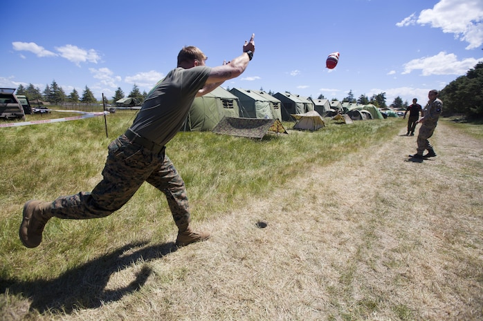 Sgt. Greg Wubben, a civil affairs non-commissioned officer with 1st Civil Affairs Group, I Marine Expeditionary Force, from Ridgefield, Wash., learns how to throw a rugby ball for the first time in the field during exercise Southern Katipo 2013 aboard Timaru, New Zealand, Nov. 16. SK13 allows our service members to collaborate with partner countries to achieve mutual security goals, address shared concerns and continue to enhance our interoperability.
