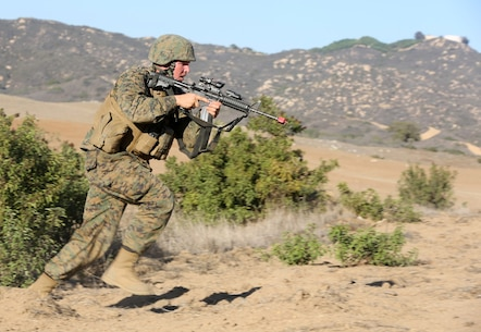 MARINE CORPS BASE CAMP PENDLETON, Calif., -- Sergeant Brandon Schroeder, platoon sergeant, Tango Battery, 5th Battalion, 11th Marine Regiment, and a native of Delta, Colo., maneuvers toward enemy role-players during a training exercise at the Mobile Immersion Trainer here, Nov. 14, 2013. The MIT is similar to the Infantry Immersion Trainer and trains Marines to operate under stressful conditions. Throughout the morning, the battery simulated operating out of a base and posted security while mock insurgents attempted to breach the area and formed riots. The artillerymen later conducted a logistics patrol and recovered a broken vehicle, countered an improvised explosive device and repelled enemy role-players during an ambush. The battery is slated to continue predeployment training before deploying to Afghanistan this winter.