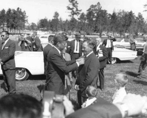 President John F. Kennedy adjusts the tie of Heber Springs Mayor William J. Allbright at the dedication of Greers Ferry Dam, Oct. 3, 1963.