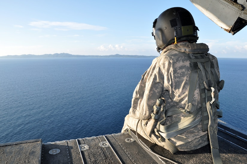 A crewchief takes in the view from the ramp of a CH-47 Chinook helicopter assigned to the 1-228th Aviation Regiment as it flies off the coast of Honduras, Nov. 19, 2013.  The helicopter crew was participating a training scenario as part of a week-long Collective Training Exercise (CTE) being condcuted by the 1-228th.  (U.S. Air Force photo by Capt. Zach Anderson)