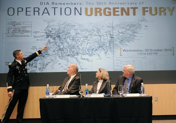 DIA Director LTG Michael Flynn annotates key positions on a map while sharing his experience and role in Operation Urgent Fury during the 30-year anniversary commemoration event Oct. 23.