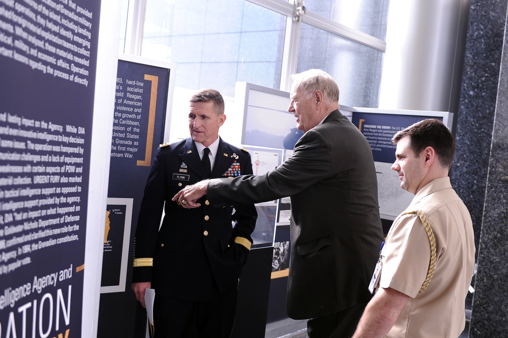 From left, current Director LTG Michael Flynn, former director LTG James Williams, and the director's executive officer discuss the Operation Urgent Fury display in the Missile Lobby after the event.