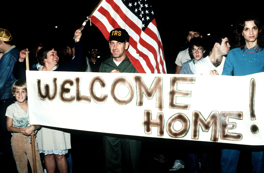 """Friends and family hold up a """"Welcome Home"""" sign for the American medical students arriving at Charleston Air Force Base Nov. 3, 1983, after being rescued in Grenada by U.S. forces."""