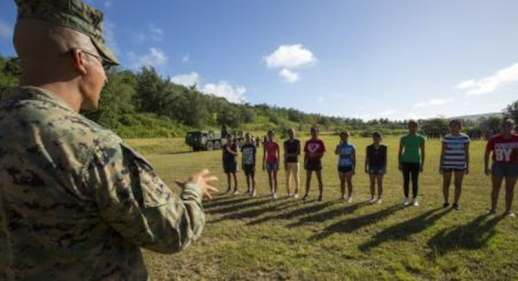 Staff Sgt. Jose R. Camberos from Los Angeles, Cali., teaches military troop movement to cadets to instill discipline Nov. 22 at the Tinian Junior Senior High School Junior Reserve Officers' Training Corps field. Cadets from TJSHS JROTC partook in a field meet with Marines and sailors to build camaraderie between one another. Camberos is operations chief of heavy equipment with Marine Wing Support Squadron 171, Marine Aircraft Group 12, 1st Marine Aircraft Wing, III Marine Expeditionary Force.