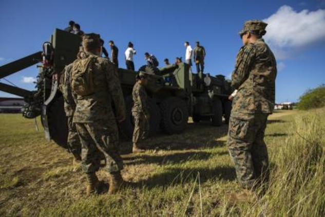 Marines give classes to cadets on the abilities and characteristics on the Logistical Vehicle Systems Replacement 15 to better help them understand the capabilities of the Marine Corps Nov. 22 at the Tinian Junior Senior High School Junior Reserve Officers' Training Corps field. Cadets from TJSHS JROTC partook in a field meet with Marines and sailors to build camaraderie between one another. The Marines are 3536s' wrecker operators with Marine Wing Support Squadron 171, Marine Aircraft Group 12, 1st Marine Aircraft Wing, III Marine Expeditionary Force.