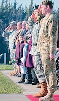 Alexandra Ghika looks to her mother, Clare, as her father, Brig. Christopher Ghika, foreground, salutes alongside Maj. Gen. Paul E. Funk II, commanding general, 1st Inf. Div. and Fort Riley, Nov. 15 at Fort Riley. Brig. Ghika was welcomed during the ceremony as the 1st Inf. Div.'s deputy commanding general for readiness by Funk.  Photo by: Amanda Kim Stairrett, 1ST INF. DIV.