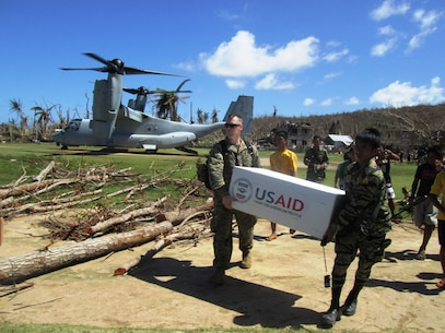 U.S. Marine Capt. Joseph White, left, of Barstow, Calif., the deputy logistics officer of the 31st Marine Expeditionary Unit and Philippine Army PFC Vic D. Victorlano carry U.S. Agency for International Development relief supplies from an MV-22 Osprey tiltrotor aircraft, Nov. 18. A bilateral assessment team landed to deliver relief and determine needs in remote areas in and near Leyte to assess the needs of people isolated by Typhoon Haiyan. U.S. military assets have delivered relief supplies provided by the U.S. Agency for International Development since the start of Operation Damayan, in support of the Government of the Philippines in the wake of Typhoon Haiyan.