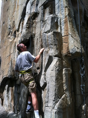 Lt. Col. Dan Oosterhous, the Academy's men's tennis coach is seen here climbing a rock wall in May. Oosterhous, a 1993 Academy graduate, suffered two strokes in late February but has been on the recovery since then. He says setting setting goals helps him face and overcome challenges.