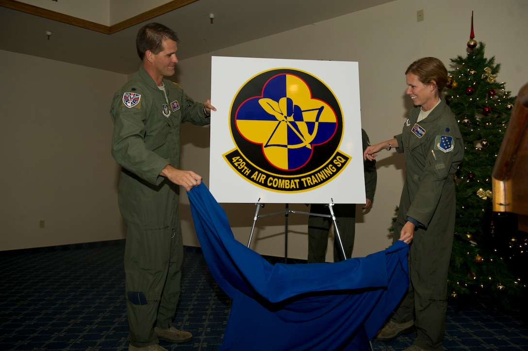 Lieutenant Col. Ken DeGraaf, Mathematics professor at the Air Force Academy, and Lt. Col. Gina Sabric, deputy commander of the 44th Fighter Group, unveil the new 429th Attack Squadron patch to be worn by flight members under the Squadrons command at Holloman Air Force Base N.M., Nov. 19. Both are former commanders of the 429th Attack Squadron. The 429th Attack Squadron was initially activated in 1917 and deactivated in 1962.(U.S. Air Force photo by Airman 1st Class Chase Cannon/Released)