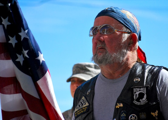 A motorcycle rider stands proudly honoring veterans during a Veteran's Day ceremony at the Panama City Rescue Mission Nov. 11. The event provided free meals to homeless veterans.