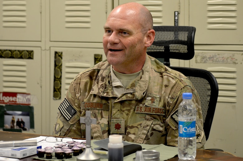 U.S. Air Force Chaplain (Maj.) Gary Coburn, 455th Air Expeditionary wing, visits the 83rd Expeditionary Rescue Squadron at Bagram Airfield, Afghanistan, Nov. 24, 2013. Coburn held a small service for Airmen assigned to the 83rd ERQS in their briefing room. Coburn is deployed from Buckley Air Force Base, Colo. (U.S. Air Force photo by Senior Airman Kayla Newman/Released)