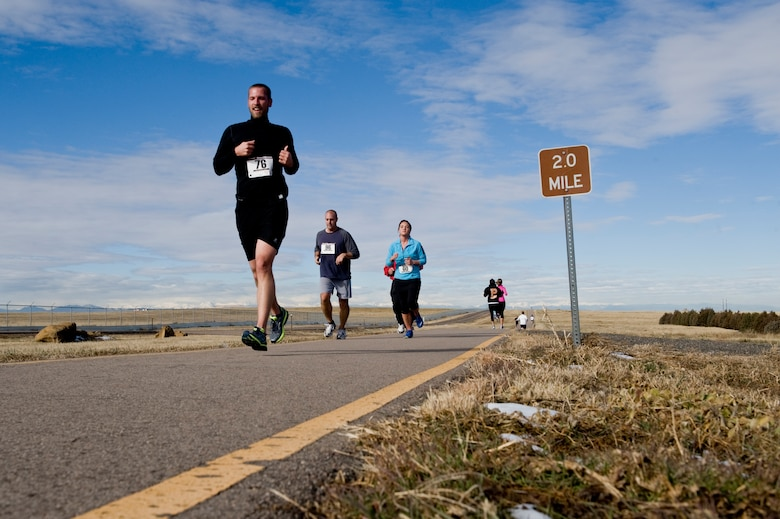 Turkey Trot competitors speed past the 2-mile marker Nov. 26, 2013, on Buckley Air Force Base, Colo. During the competition, 19 Team Buckley members competed with the fastest runners in each category given turkeys as prizes.  (U.S. Air Force photo by Senior Airman Phillip Houk/Released)