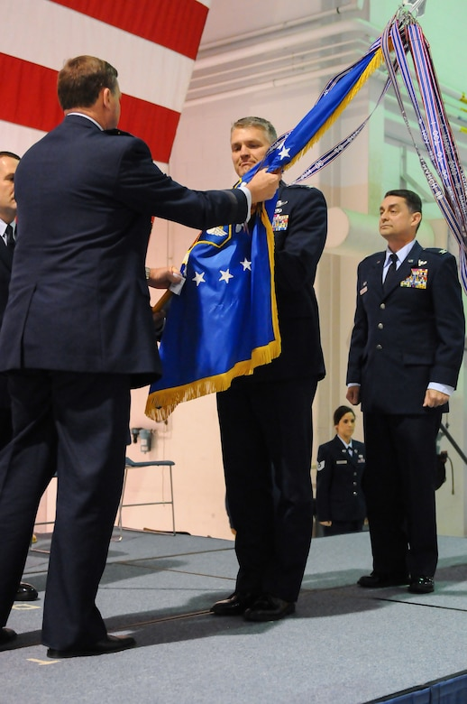 Col. Barry Gorter (center), incoming commander of the 123rd Airlift Wing, accepts the unit guidon from Maj. Gen. Edward Tonini, Kentucky's adjutant general, during a change-of-command ceremony at the Kentucky Air National Guard Base in Louisville, Ky., Nov. 24, 2013, as Col. Warren Hurst (right), the outgoing wing commander, observes. Hurst has been named Kentucky's assistant adjutant general for Air. (U.S. Air National Guard photo by Staff Sgt. Vicky Spesard)