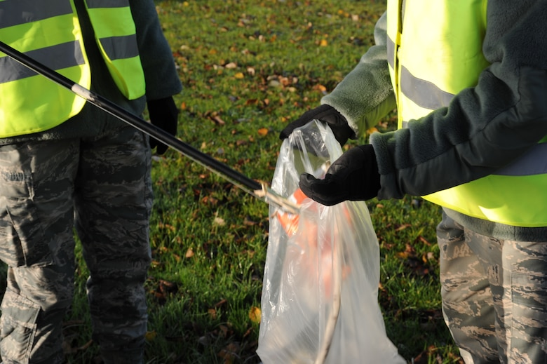 SPANGDAHLEM AIR BASE, Germany -- An Airman puts a piece of trash in a trash bag during a morning trash route along Perimeter Road Nov. 25, 2013. Eifel Pride is a year-round program used for base beautification by first-term Airmen. The program also allows the Airmen to attend the many initial appointments and briefings. (U.S. Air Force photo by Airman 1st Class Dylan Nuckolls/Released)