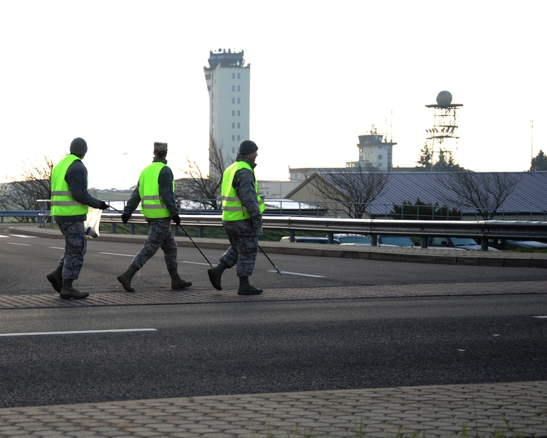 SPANGDAHLEM AIR BASE, Germany -- Airmen look for trash along Arnold Boulevard during a morning trash route Nov. 25, 2013. Eifel Pride is a two-week course where first-term Airmen keep the base clean while settling in to their first duty station. (U.S. Air Force photo by Airman 1st Class Dylan Nuckolls/Released)