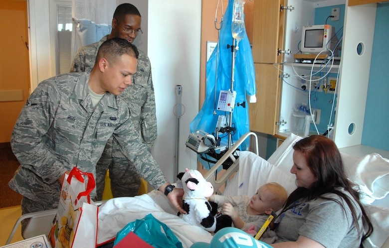 Airman Evan Rios (left) and Master Sgt. Don Mitchell deliver a stuffed cow to Madeline Dougherty, 2, who is appropriately nicknamed 'moo-moo', during a visit to Children's Hospital & Medical Center Nov. 20, 2013, in Omaha, Neb. The Airmen were part of a group of 12 volunteers who delivered more than 90 stuffed animals on behalf of the Air Force Sergeants Association, Chapter 984. These animals included an internal pouch where patients could place a star after making a wish. Rios is a 55th Strategic Communications Squadron communications operator and Mitchell is a 55th Force Support Squadron manpower analyst. Both are stationed at Offutt AFB, Neb.