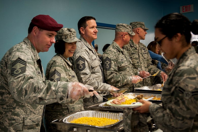 Senior NCOs and officers serve food to Airmen during the Thanksgiving luncheon Nov. 21, 2013, at Moody Air Force Base, Ga. The Thanksgiving meal enforced esprit de corps and supported Airmen who celebrate the holidays without their families.