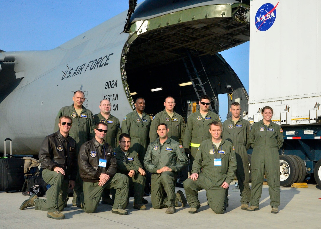 Aircrew from the 709th Airlift Squadron and crew chiefs from the 512th Maintenance Group pose for a group shot following the safe unload of the Global Precipitation Measurement Satellite Nov. 24, 2013, at Kitakyushu Airport in Japan. The crew worked hand-in-hand with NASA officials to ensure the delicate cargo was properly cared for during transport. (U.S. Air Force photo/Tech. Sgt. Jeremy Larlee)
