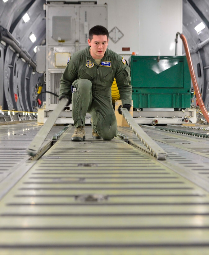 Senior Airman Travis Shea prepares the cargo floor of a C-5M Super Galaxy for the Global Precipitation Measurement Satellite's support equipment Nov. 21, 2013, at Joint Base Andrews, Md. The mission to deliver the satellite to Japan was Shea's first. Shea is a 709th Airlift Squadron loadmaster student. (U.S. Air Force photo/Tech. Sgt. Jeremy Larlee)