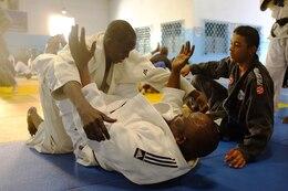 Malick oversees a Brazilian jiu jitsu drill performed by two judo black belts, including Judo Club Fanta Keita founder and head instructor Assane Diop, on top, during a seminar at the Senegal National Dojo in Dakar, Senegal on Nov. 9, 2013.