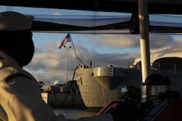 Petty Officer 2nd Class Jon-Pierre Stewart, drives the Remembrance barge past the USS Missouri here Nov. 25. Stewart was in charge of transporting members of the Chaplain Corps to the USS Arizona Memorial during a barge tour in remembrance of the fallen victims of the attack on Pearl Harbor.
