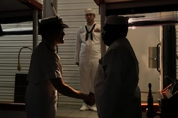 Petty Officer 1st class Scott Burroughs, a boatswains mate with U.S. Pacific Fleet, awaits Rear Adm. Margaret Grun Kibben, Chaplain of the Marine Corps (left), as she shakes hands with Petty Officer 2nd class Jon-Pierre Stewart, an engineer with PACFLT, before she disembarks the Remembrance barge at the end of the tour here Nov. 25. Members of the Chaplain Corps visited the USS Arizona Memorial in order to pay tribute to the fallen heroes who lost their lives during the attack on Pearl Harbor, Dec. 7, 1941.