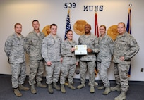 Airman 1st Class Katelyn Karr, 509th Munitions Squadron armament systems team member, receives the Top III MVP award for November at Whiteman Air Force Base, Mo., Nov. 21, 2013. Some of the accomplishments that contributed to her award include supporting more than 100 veterans for a wheelchair washing initiative and completing her career development course books three months early. (U.S. Air Force photo by Staff Sgt. Nick Wilson/Released)