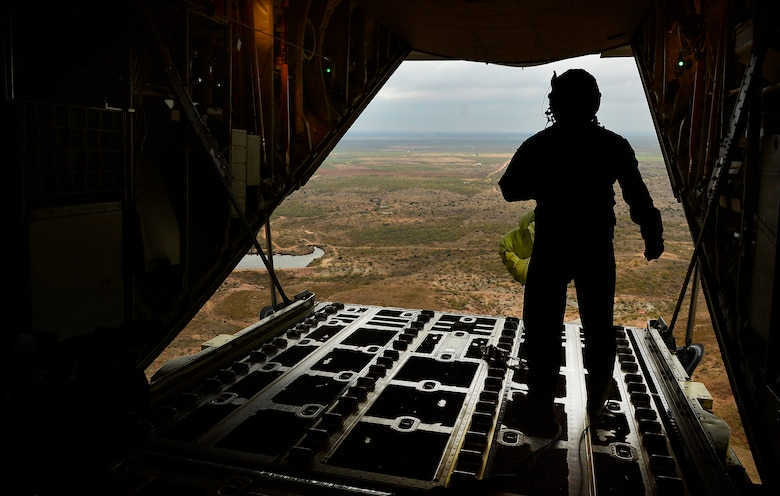 U.S. Air Force Senior Airman Matthew Bihlajama, 40th Airlift Squadron loadmaster, releases cargo from a C-130J Super Hercules at a drop zone Nov. 21, 2013, during Impact Day near Bronte, Texas. Impact Day gave maintainers from the 317th Airlift Group the opportunity to fly aboard a C-130J as it dropped cargo bundles at a designated drop zone. (U.S. Air Force photo by Staff Sgt. Vernon Young Jr./Released)