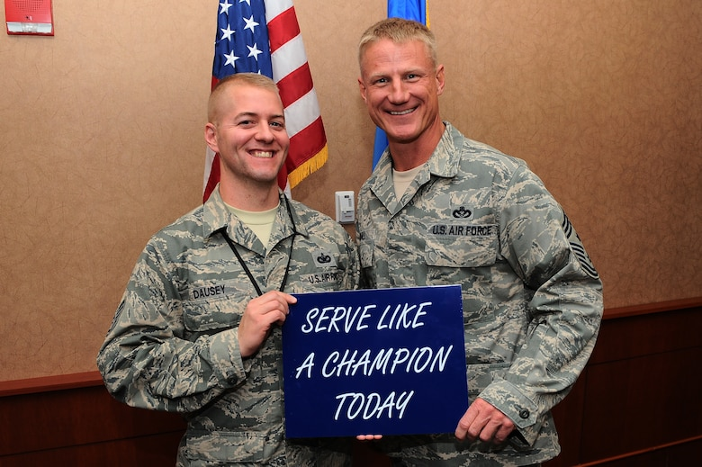 """Tech. Sgt. Jeffrey Dausey, 460th Space Wing Antiterrorism Office, receives the """"Serve Like A Champion"""" Award from Chief Master Sgt. Craig S. Hall, 460th SW command chief, Nov. 22, 2013, at the 460th SW headquarters building on Buckley Air Force Base, Colo. Dausey received this award for demonstrating excellent morals and service. This is the third award Hall has given that rewards and encourages Team Buckley members to serve like a champion. (U.S. Air Force photo by Senior Airman Phillip Houk/Released)"""