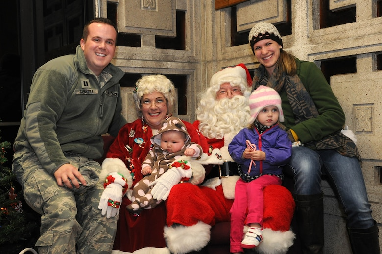Capt. Chase Gunnell, 11th Wing Assistant Staff Judge Advocate, and his family pose for a photo with Santa Claus and Mrs. Claus during the annual Christmas tree and Menorah lighting ceremony at Joint Base Andrews, Md., Nov. 26, 2013. During the night children were given the chance to talk to Santa and tell him what they wanted for Christmas. (U.S. Air Force photo/Airman 1st Class Ryan J. Sonnier)