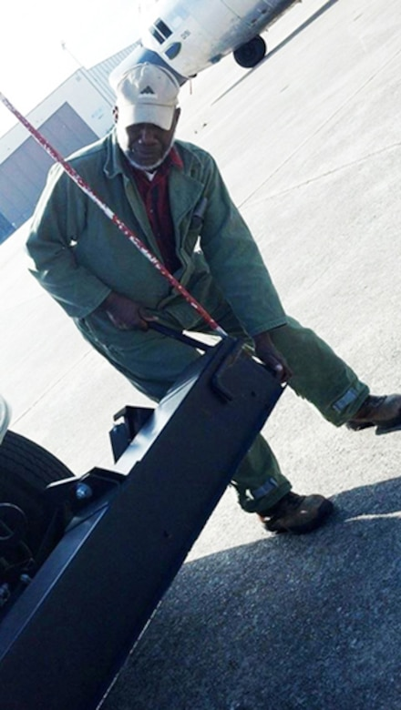 Jerome Bryant inspects a horizontal magnet attached to the front of a Tymco street sweeper truck. The magnet can pick up any small metal pieces found on pavement. (U.S. Air Force photo by Jenny Gordon)