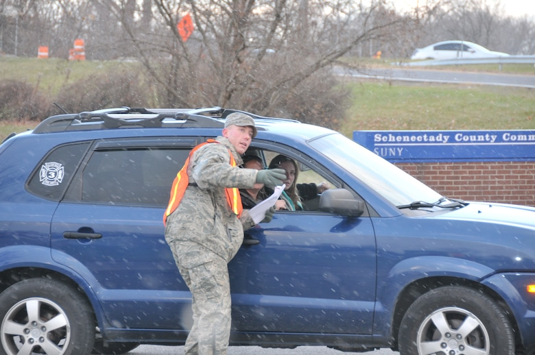 SCHENECTADY, N.Y. -- Tech. Sgt. Matthew Begin, 109th Maintenance Group, directs a parade participant where to park in preparation for the 46th annual Gazette Holiday Parade on Nov. 23, 2013. About 20 volunteers with the 109th Airlift Wing, including some family members, volunteered to help usher the floats in for the parade. (Air National Guard photo by Tech. Sgt. Catharine Schmidt/Released)
