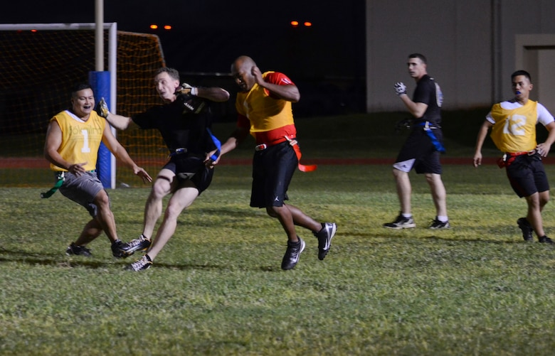 Shane Szymczak, 94th Army Air and Missile Defense Command, tries to evade defenders during an intramural flag football game Nov. 25, 2013, on Andersen Air Force Base, Guam. The 94th AAMDC defeated 22nd Space Operations Squadron Detachment 5, 40-0. (U.S. Air Force photo by Senior Airman Marianique Santos/Released)