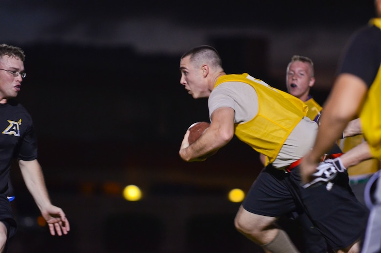 Mark Massey, 22nd Space Operations Squadron Detachment 5, runs past other players during an intramural flag football game Nov. 25, 2013, on Andersen Air Force Base, Guam. 94th Army Air and Missile Defense Command defeated 22nd SOPS Det 5, 40-0. (U.S. Air Force photo by Senior Airman Marianique Santos/Released)