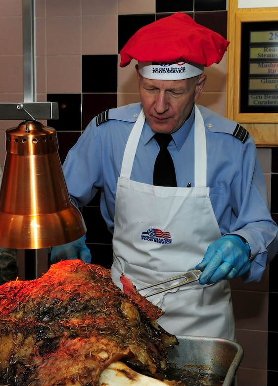 Royal Air Force Sqn. Ldr. Rick Fryer, RAF Mildenhall station commander, carves roast beef during the Thanksgiving lunch served in celebration of the American holiday Nov. 28, 2013, at the Gateway Dining Facility on RAF Mildenhall, England. The dining facility hosted the event, where several distinguished visitors joined the dining facility staff to serve lunch to approximately 250 members of Team Mildenhall. (U.S. Air Force photo by Senior Airman Kate Maurer/Released)